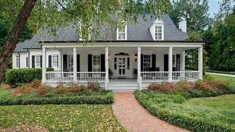 Beautiful white house with gray roof and shrubs and trees